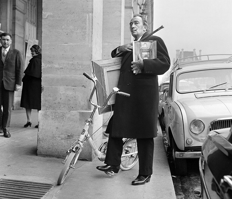 Salvador Dali delivering paintings on a Graziella folding bike